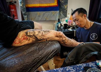 Dong Dong bei der Arbeit am Bein eines Kunden auf dem Spiekerooger Tattoo-Treff